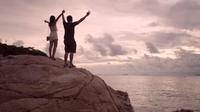 vídeos y material grabado en eventos de stock de amantes en el mar, felices por la libertad en la playa. - roca