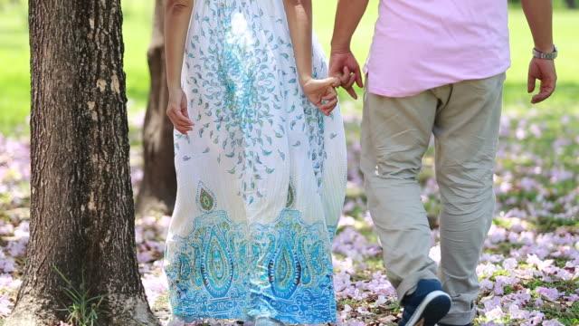 Lovers walking in garden , holding hands