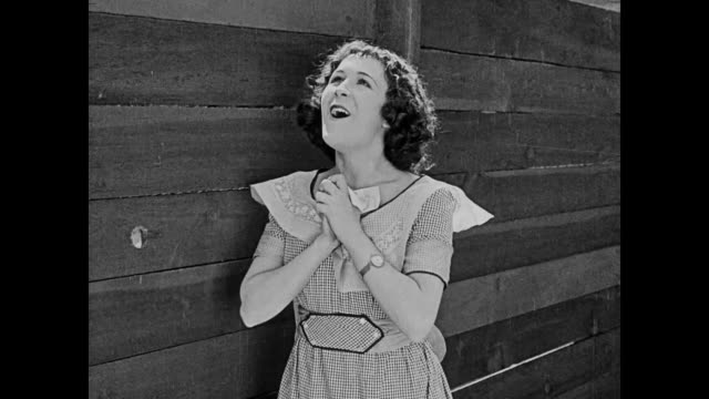 Lovesick Buster Keaton declares his love for happy woman on the other side of fence