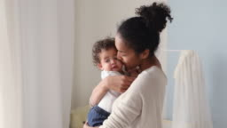 Loving african mum holding cute baby daughter kissing small kid