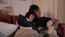 loving asian chinese couple watching movies while eating popcorn at home