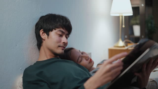 loving asian couple reading a book while relaxing on the bed at home - pajamas stock videos & royalty-free footage