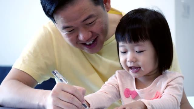 Liebender Vater asiatischen lehrt Kleinkind Tochter, wie man schreiben