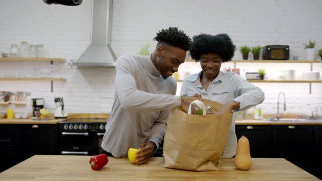 loving black couple at home unpacking their groceries while talking and smiling - paper bag stock videos & royalty-free footage