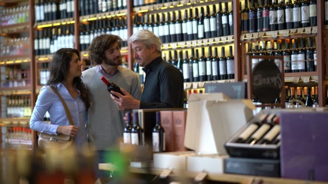 Loving couple at a wine store asking the properties of a wine to the business owner of the winery all smiling