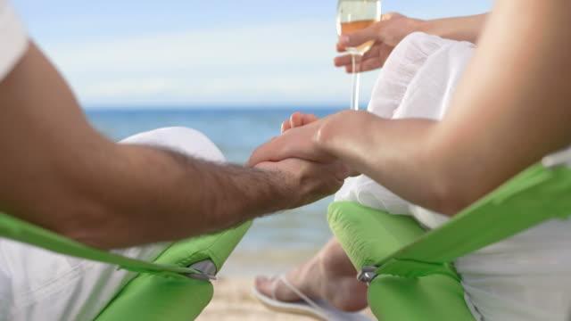 vídeos de stock, filmes e b-roll de hd: loving casal bebendo champanhe na praia - cadeira dobrável