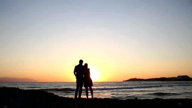 Verliefde paar omarmen op het strand bij zonsondergang