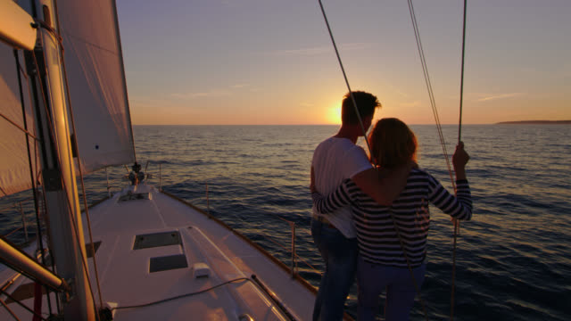 SLO MO Loving couple enjoying the sailing at sunset