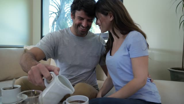 Loving couple having breakfast and woman leaning her head tenderly on her partner while he serves the coffee
