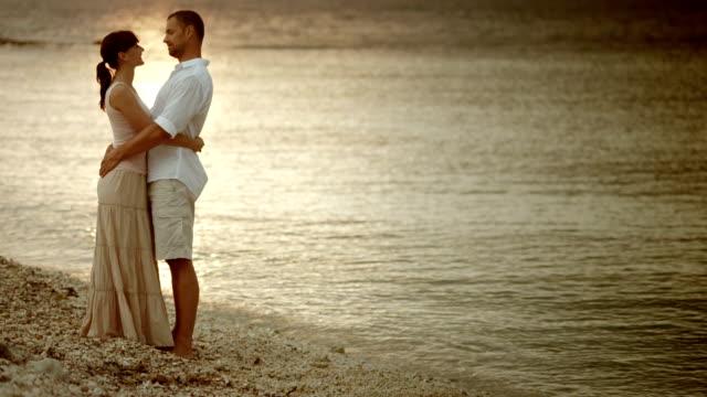 vídeos y material grabado en eventos de stock de foto de una pareja abrazándose y hablando en el mar - falda