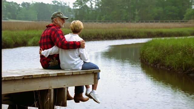 vídeos de stock, filmes e b-roll de a loving couple hugs and talks on a river dock. - pântano salgado