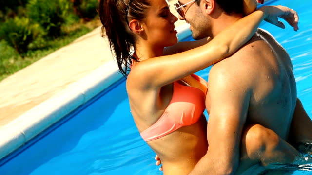 Loving couple in a swimming pool.