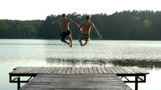 vídeos de stock e filmes b-roll de loving couple jumping into lake - amor