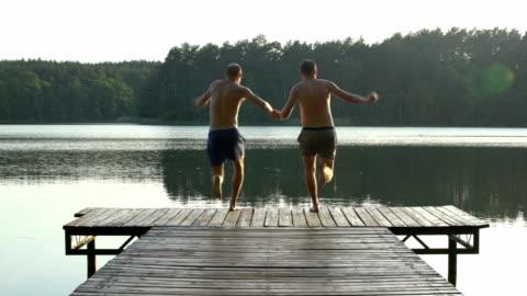 coppia amorevole che salta nel lago - young couple video stock e b–roll