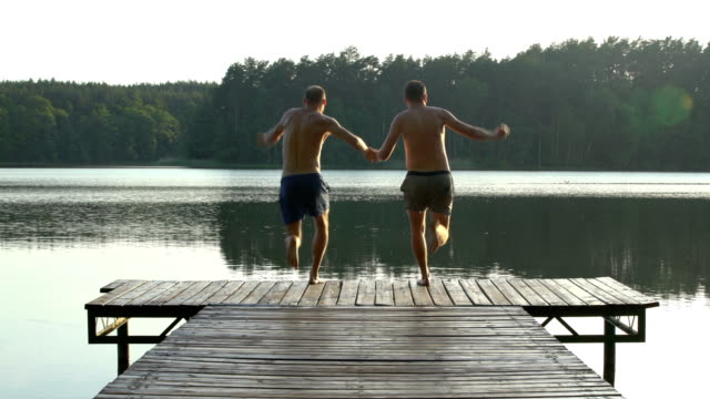 loving couple jumping into lake - pier stock videos & royalty-free footage