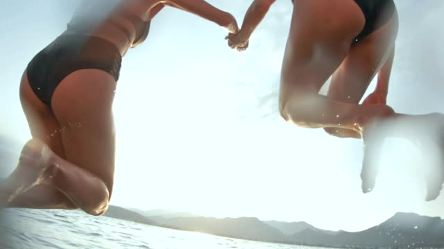 loving couple jumping into sea - pier stock videos & royalty-free footage
