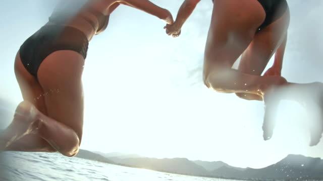 vídeos de stock, filmes e b-roll de casal apaixonado, saltar para o mar - lago