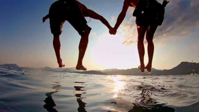 愛するカップルが海に飛び込む - ゲイ点の映像素材/bロール