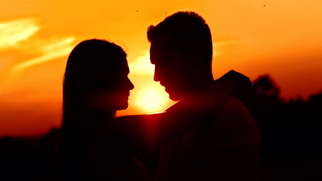 hd: loving couple kissing at sunset - back lit woman stock videos & royalty-free footage