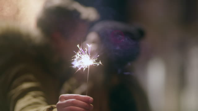 vídeos de stock e filmes b-roll de cu loving couple kissing while holding a sparkler - affectionate