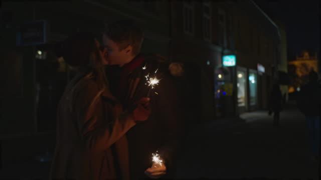 Liebespaar Küssen und hältst Wunderkerzen