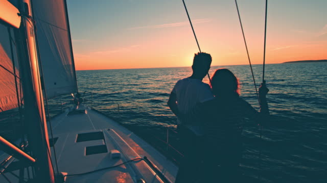 WS Loving couple looking at the sunset on a sailing sailboat