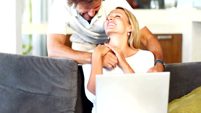 Loving couple on a sofa with laptop
