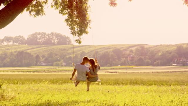 slo mo liebespaar auf einer baum-schaukel - gelassene person stock-videos und b-roll-filmmaterial