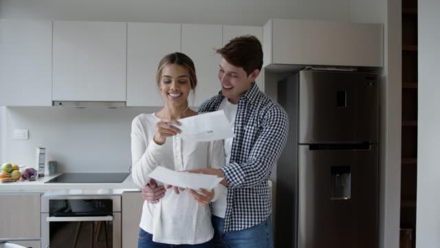 liebespaar öffnet die post zusammen, während mann hält frau an ihrer taille lachen und reden - post stock-videos und b-roll-filmmaterial