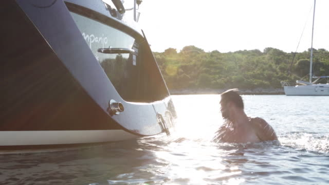 vidéos et rushes de loving couple playing in water at back of boat - embrasser sur la bouche