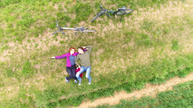 aerial loving couple relaxing in the countryside - reclining stock videos and b-roll footage