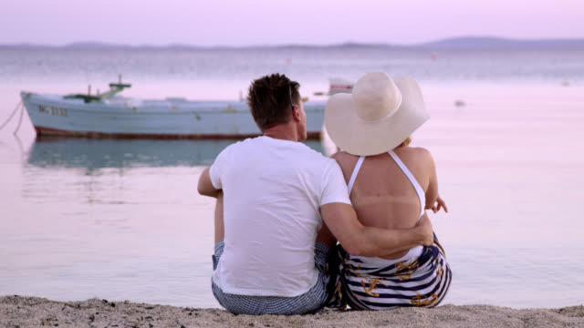 WS Loving couple relaxing on a beach at dusk
