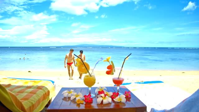 vídeos y material grabado en eventos de stock de ms amoroso par relajante en la playa tropical - tumbona
