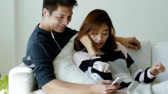Couple d'amoureux se reposer sur le canapé et profiter de la musique à la maison