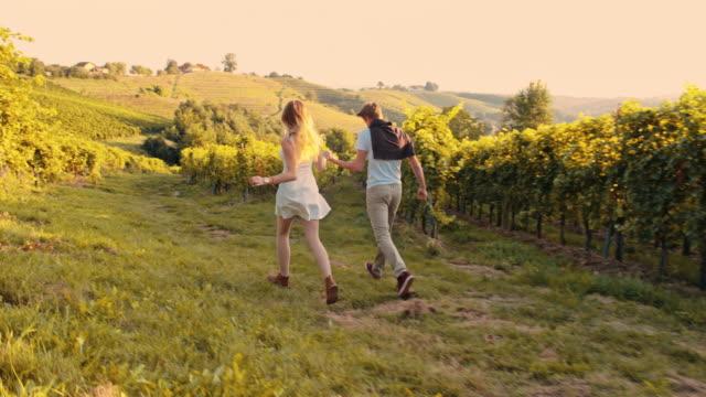 slo mo loving couple running in the vineyard - prekmurje stock videos & royalty-free footage