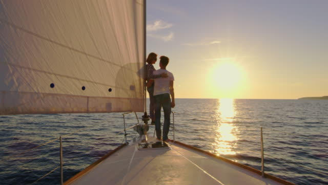 slo mo loving couple sailing the sea at sunset - ship's bow stock videos & royalty-free footage