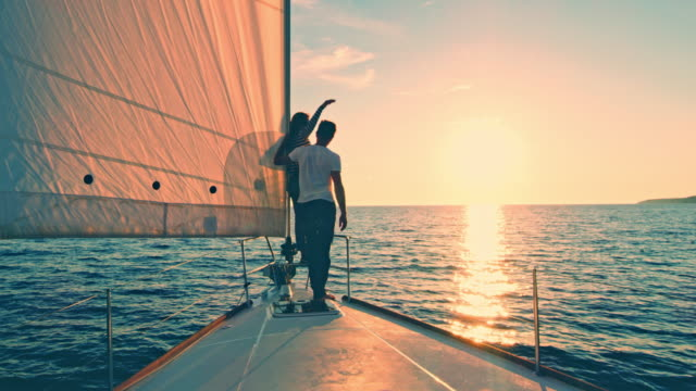 ws loving couple sailing the sea at sunset - ponte di una nave video stock e b–roll