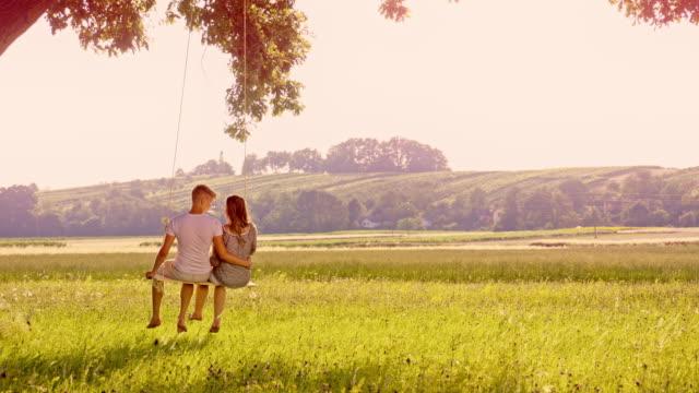 SLO MO Loving couple swinging on a tree swing