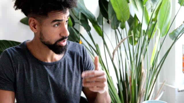 stockvideo's en b-roll-footage met verliefde paar praten terwijl handen thuis - kamerplant