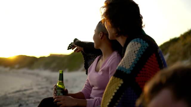 loving couple toasting beer bottles at beach - blanket stock videos & royalty-free footage