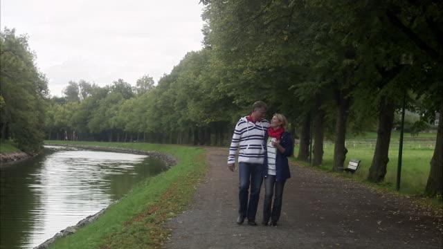 loving couple walking by a canal, sweden. - gemeinsam gehen stock-videos und b-roll-filmmaterial
