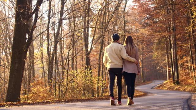 SLO MO verliefde paar wandelen door herfst bos