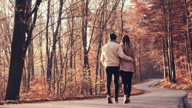 SLO MO Loving couple walking through autumn forest
