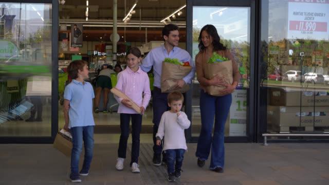 vidéos et rushes de couples affectueux avec leurs trois enfants quittant le supermarché après avoir acheté des épiceries chacun portant quelque chose tout en parlant et souriant - sachet en papier