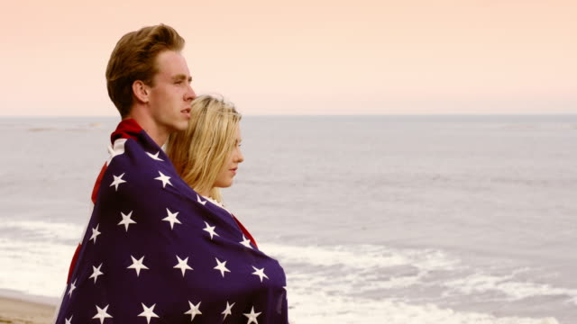 loving couple wrapped in stars and stripes at the beach 4k - vesper stock stock videos & royalty-free footage