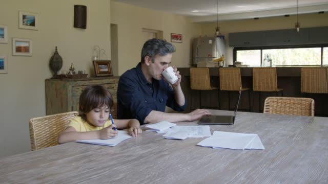 stockvideo's en b-roll-footage met liefdevolle papa die aan laptop werkt en koffie die bij zijn zoon glimlacht terwijl hij trekt - eetkamer