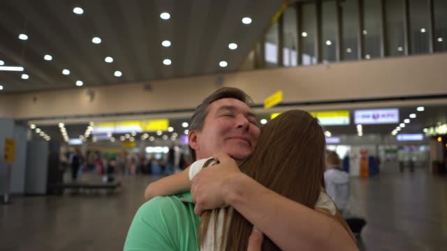 vídeos y material grabado en eventos de stock de hija amorosa abrazando a su padre en el aeropuerto mientras él la besa adiós - divorcio
