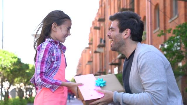 vídeos de stock, filmes e b-roll de filha loving que surpreende seu paizinho com um presente e um cartão para o dia de pai - receber