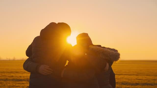 vidéos et rushes de famille aimante de slo mo avec trois étreintes d'enfants sur une prairie au coucher du soleil - vêtement chaud