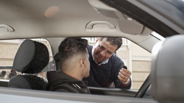 Loving father giving son car key before first driving experience
